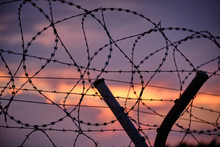 Closeup Of A Fence With Razor Wire And In Front Of A Sunset