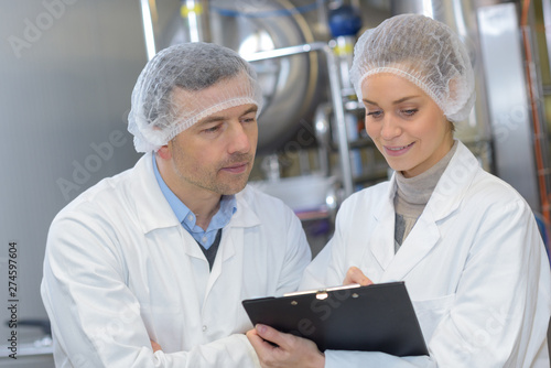Fototapeta male and female quality control workers lookinf at clipboard obraz