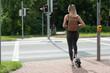 canvas print picture - Junge frau mir e-scooter auf radweg an kreuzung mit ampel