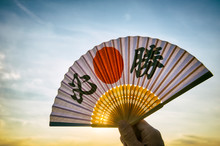 Hand Of Japanese Sports Supporter Holding A Fan Decorated With Kanji Characters Spelling Out Hissho (English Translation: Certain Victory) At Sunrise