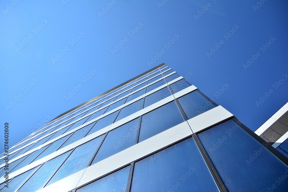 Fototapety, obrazy: New office building in business center. Wall made of steel and glass with blue sky.