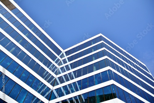 Fotobehang Aan het plafond New office building in business center. Wall made of steel and glass with blue sky.