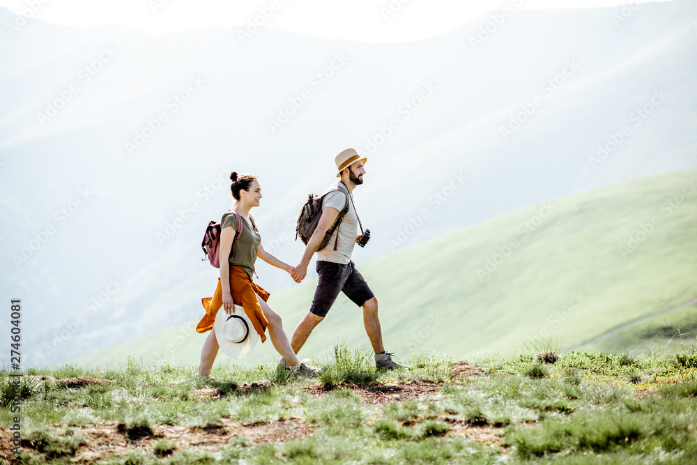 Fototapety, obrazy: Beautiful couple walking with backpacks on the green meadow, while traveling in the mountains during the summer time