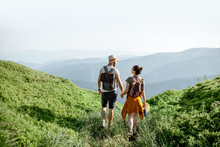 Beautiful Couple Walking With Backpacks On The Green Meadow, While Traveling High In The Mountains During The Summer Time. Rear View