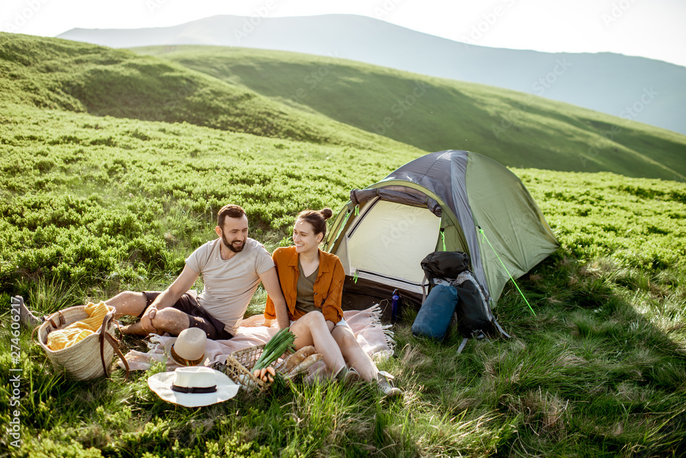 Fototapety, obrazy: Young and cheerful couple having a picnic at the campsite while traveling high in the mountains during the sunset