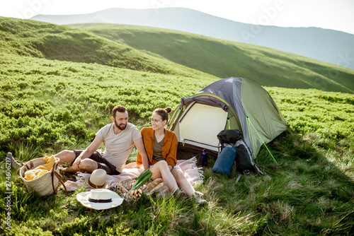Young and cheerful couple having a picnic at the campsite while traveling high in the mountains during the sunset