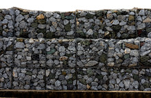 Retaining Stone Wall Next To The Road. Protection Fence Or Wall Made Of Gabions With Stones. Stone Wall With Metal Grid As Background. Stone Floor Texture, A Wall Called A Gabion. On White Background,