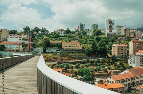 Fotografija  Footbridge over valley with apartment building and trees