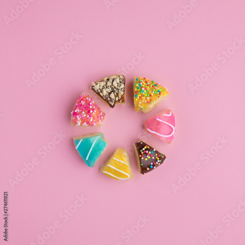 Donut shape made of cut donut slices on pink background. Fototapet