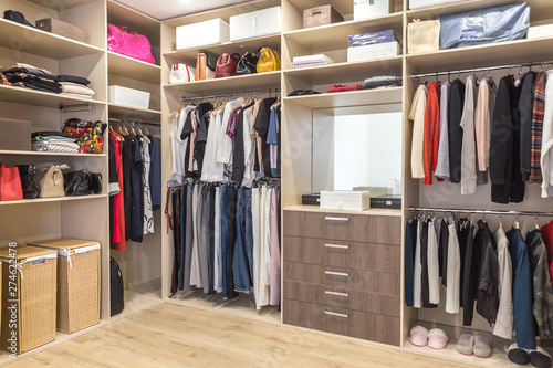 Big wardrobe with different clothes for dressing room Fototapet