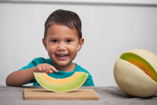 A Happy Young Kid With Cute Smile Points To His Slice Of A Honeydew Melon He Is About To Eat As Part Of A Healthy Snack.