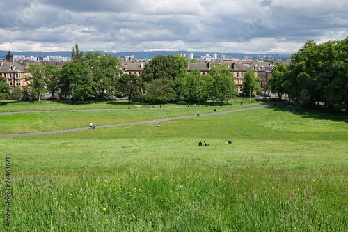 Queen's Park in Glasgow, Scotland, is shown on a cloudy day. The park was developed in the 1800s, named in honor of Mary, Queen of Scots, and is a focal point of the local community.