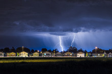 Lightning Bolts Over A Neighborhood At Night