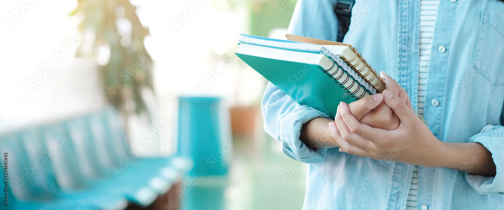 Fototapeta Student girl holding books and carry school bag while walking in school campus background, education, back to school concept banner