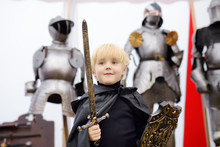 Portrait Of A Cute Little Boy Dressed As A Medieval Knight With A Sword And A Shield On Background Of Knight's Armor.
