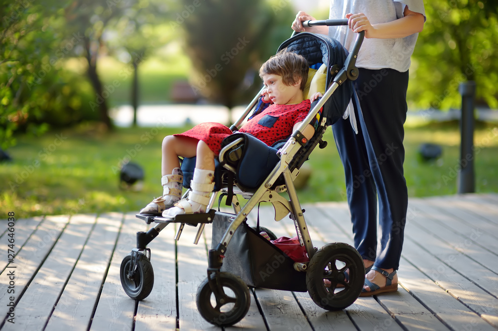 Fototapety, obrazy: Woman with disabled girl in a wheelchair walking in the Park summer. Child cerebral palsy. Family with disabled kid.