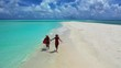 two attractive young women running on sandbar of Mansalangan in Balabac, aerial shot in Palawan, Philippines, friendship or homosexual relationship