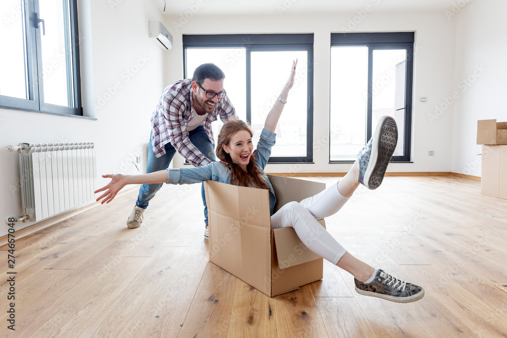 Fototapeta Young couple in new empty room. She is sitting on card box while he pushing her from behind