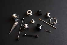 Diverse Set For Piercing On A Dark Background, Ear Tunnels, Tunnels And Earrings For The Ears And Tongue Close-up