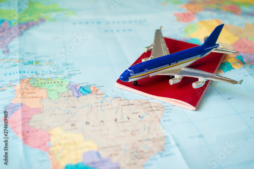 Poster de jardin Amérique du Sud toy aircraft and neutral passport on the world map. travel and air transportation concept, flight to south america, trip by plane, booking flights