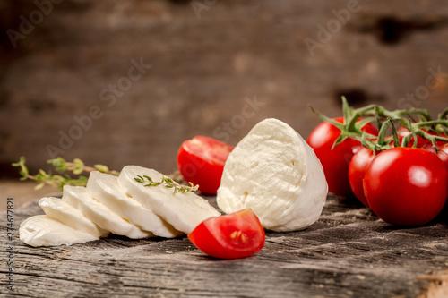 Fotografía  Mozzarella cheese, basil and tomato cherry on slate stone board, copy space
