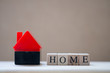 Wooden blocks with the word HOME stands near the house