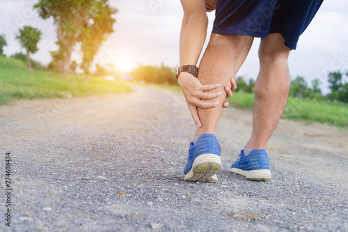 Obraz Runner sportsman holding leg in pain after suffering muscle injury during running workout training. - fototapety do salonu