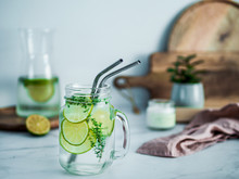 Cold Drink In Mason Jar With Metal Straws On Kitchen Table. Lemonade Or Detox Water With Lime And Thyme In Glass Jar Wit Metal Straw Indoor. Recyclable Straws, Zero Waste Concept