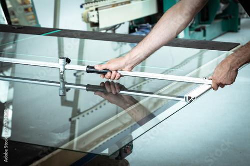 A worker cuts glass in a glass workshop