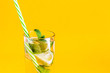 canvas print picture - Fresh summer lemonade with water, lime and mint in a glass tumbler with a straw on a yellow background. Cold, refreshing summer cocktail close up. Fresh drink with copy space
