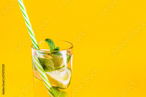 Fotografie, Obraz  Fresh summer lemonade with water, lime and mint in a glass tumbler with a straw on a yellow background