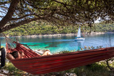 Woman relaxing in the hammock on a hot sunny day on the island lastovo, croatia