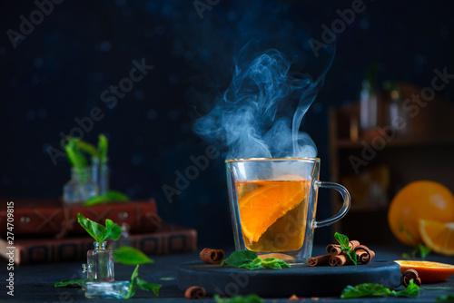 Recess Fitting Tea Double wall glass cup with citrus tea, cinnamon, and mint leaves. Steam in dark food photography with copy space.