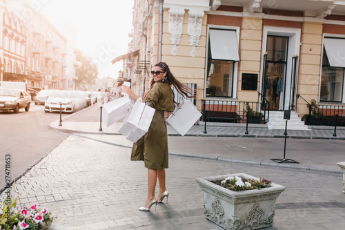 Full-length portrait from back of inspired woman in sparkle shoes enjoying shopping. Attractive shopaholic girl with black hair looking over shoulder while standing on the street. - 274711653