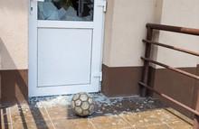 A Soccer Ball Broke The Window. Football And Broken Window Glass. Close-up, Selective Focus.