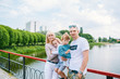 A family with a small children is photographed in a park on the shore of a river and on a bridge.