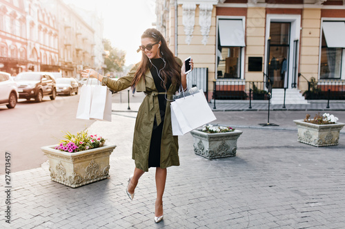 Keuken foto achterwand Muziekwinkel Full-length portrait of amazing woman in sparkle shoes and green coat carrying packages and smiling. Photo of slim happy girl in sunglasses hurrying home after shopping, walking by flowerbed.