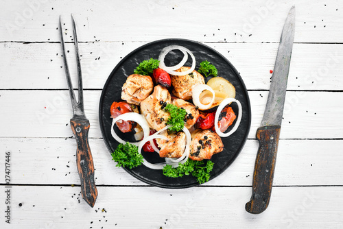 Barbecue chicken on skewers with onions and tomatoes. Barbecue. Top view. Free space for your text. Rustic style.