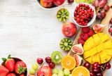 Colorful fruits background, cut mango, strawberries raspberries oranges plums apples kiwis grapes blueberries cherries, on white table, copy space, top view, selective focus
