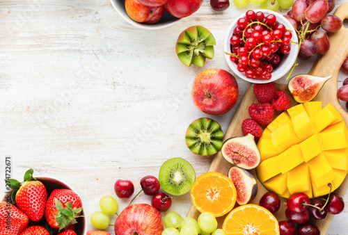 Colorful fruits background, cut mango, strawberries raspberries oranges plums apples kiwis grapes blueberries cherries, on white table, copy space, top view, selective focus - 274722671