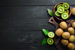 canvas print picture - Fresh kiwi and green leaves on the table. Rustic style. Fruits. Top view. Free space for text.