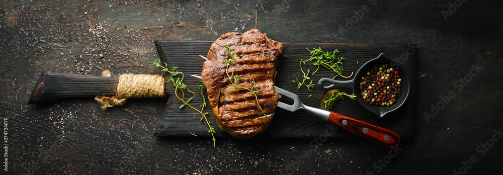 Fototapety, obrazy: Grilled ribeye beef steak, herbs and spices on a dark table. Top view. Free space for your text.