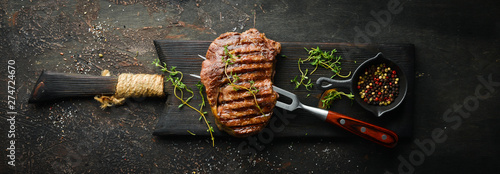 Fototapeta Grilled ribeye beef steak, herbs and spices on a dark table. Top view. Free space for your text. obraz