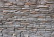 Dark gray and brown exterior wall cladding made of irregular natural stones. Stone paneling, background and texture.