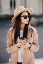 Fashion Outdoor Photo Of Beautiful Girl With Dark Hair In Elegant Beige Coat Walking By Street With A Cup Of Coffee