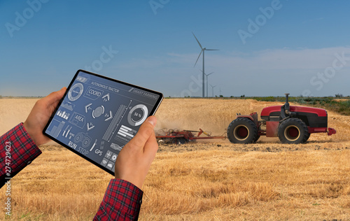 Aufkleber - A farmer with digital tablet controls an autonomous tractor on a smart farm
