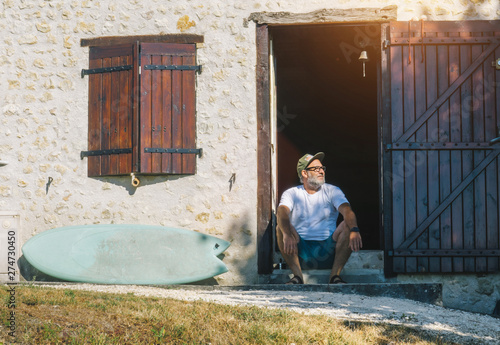 Foto auf Gartenposter Lineale Wachstum Mature Surfer Man check the waves in front of his old beach house