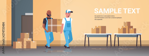 Obraz two couriers in uniform carrying cardboard box package mail express delivery service concept mix race industrial factory workers working in stockroom of storehouse flat full length horizontal - fototapety do salonu