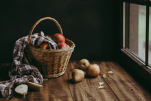 Autumn Composition With Yellow Flowers And Apples In A Wicker Basket And Pears On A Wooden Background
