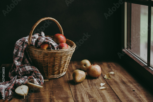 Fotografía  Autumn composition with yellow flowers and apples in a wicker basket and pears o